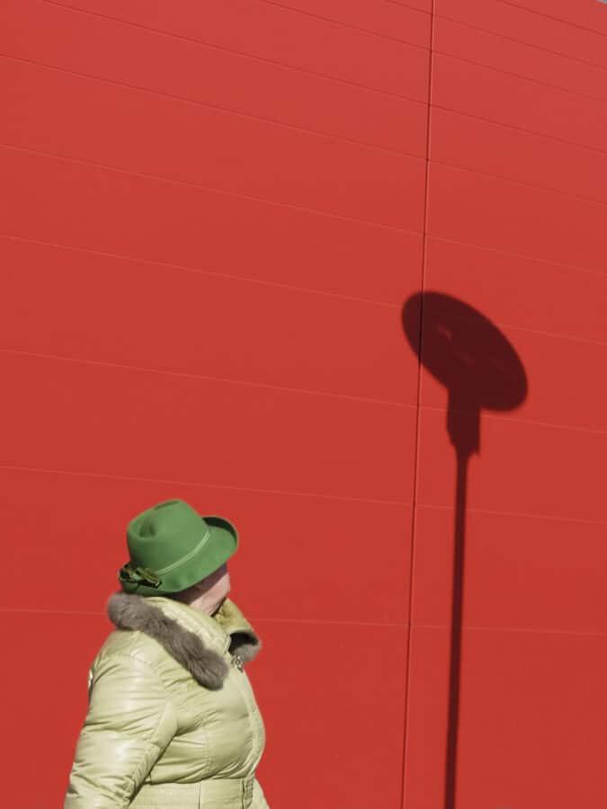 Guido-Klumpe-Minimalistisch-AEine Frau mit grünem Hut vor roter wand mit Lampe